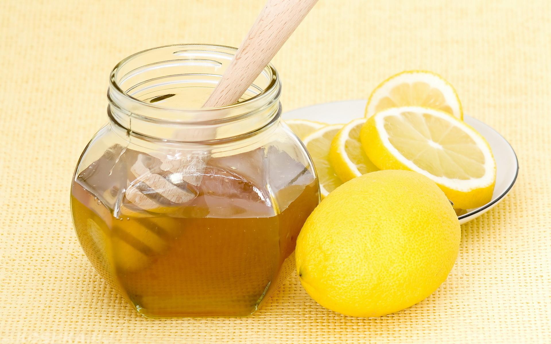 Банка мёда и нарезанный лимон на блюдце